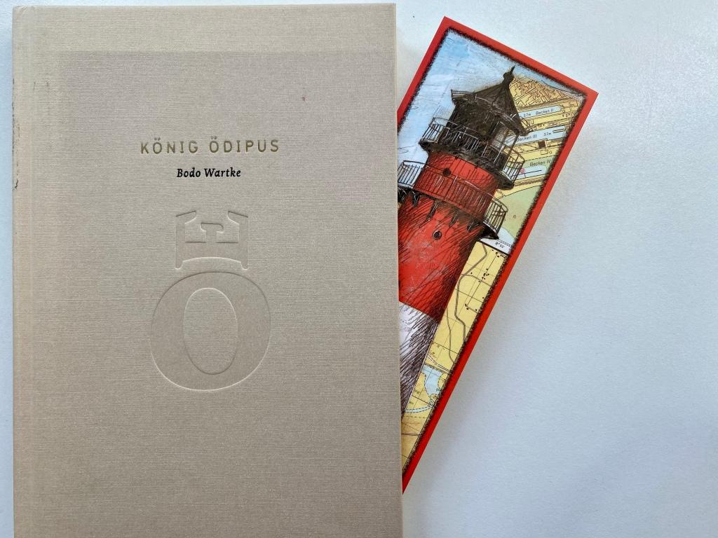 Zu sehen ist links das Buchcover aus dem nach rechts heraus ein Leuchtturm-Lesezeichen ragt